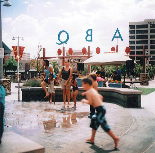 Parents and children playing in the ABQ Uptown fountain