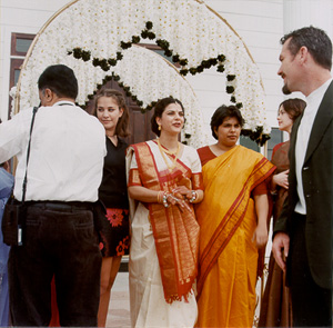 Mora greets guests in front of the flower arch